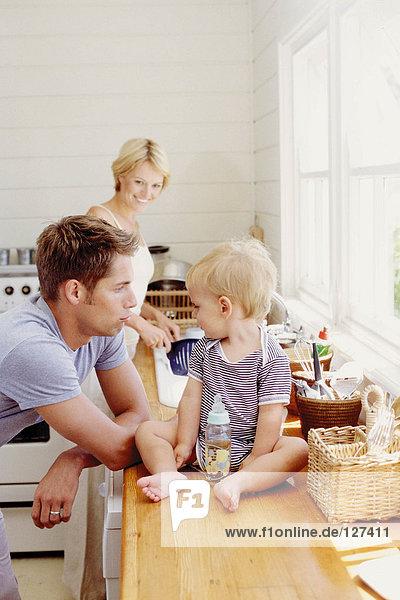 Junge Eltern mit Kind in der Küche