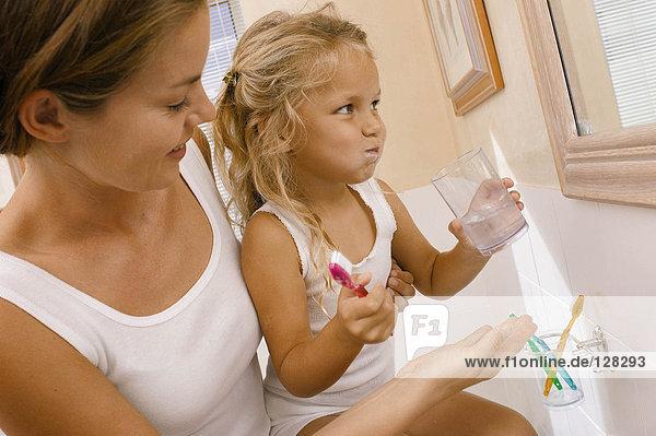 Mutter hilft Tochter beim Zähneputzen