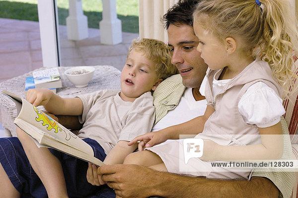 Vater und Kinder betrachten Bilderbuch