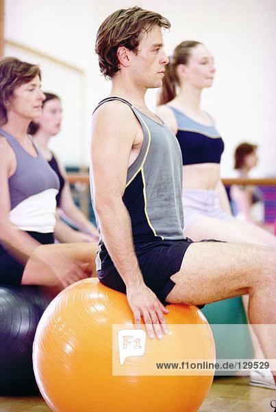Mann auf Fitnessball sitzend Mann auf Fitnessball sitzend