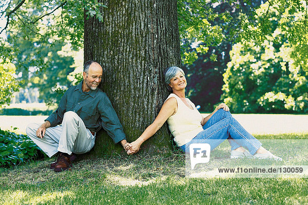 Paar sitzt unter einem Baum