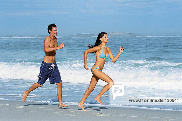 Woman and man jogging on the beach