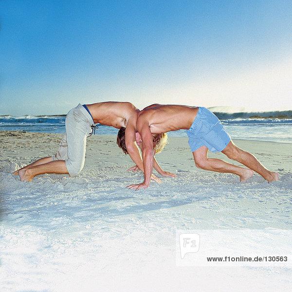 Men wrestling on the beach