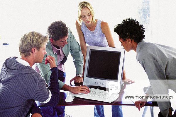 Männer und Frauen  die den Computer benutzen