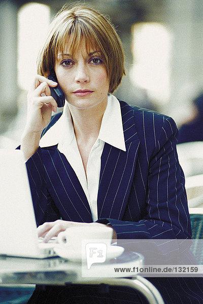 Geschäftsfrau mit Laptop und Handy im Cafe Geschäftsfrau mit Laptop und Handy im Cafe