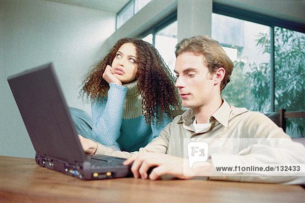 Mann und Frau zu Hause mit Laptop