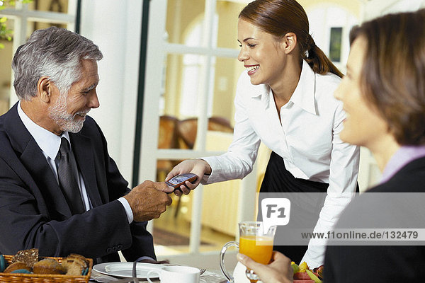 Kellnerin übergibt Handy an Geschäftsmann