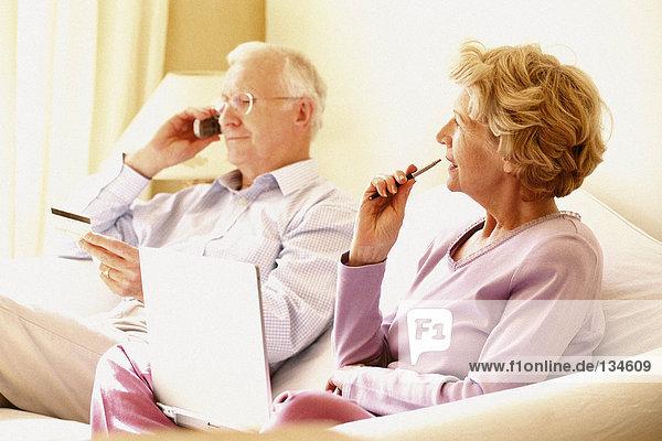 Mann auf dem Handy und Frau mit Laptop-Computer