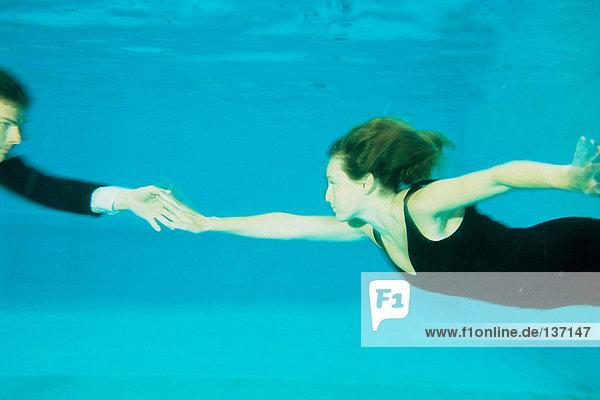 Ein Paar  das im Schwimmbad tanzt.