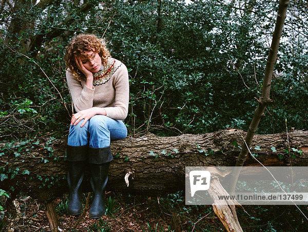 Frau auf einem Baumstamm sitzend