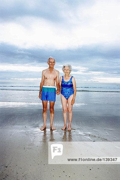 Ein reifes Paar  das am Strand Händchen hält.