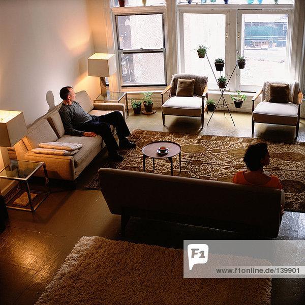 Paar im Wohnzimmer getrennt sitzend