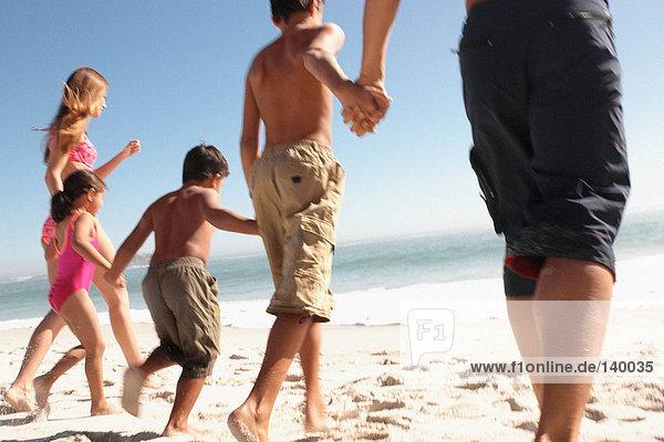 Familie hält Hände am Strand