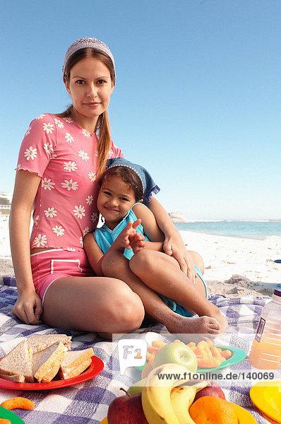 Mutter und Tochter beim Picknick am Strand