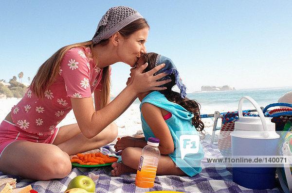 Mutter küsst Tochter am Strand