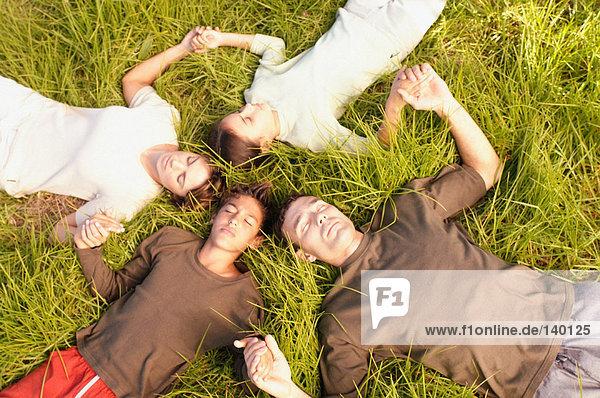 Menschen liegen im Kreis auf Gras
