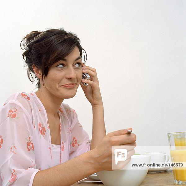 Frau am Telefon beim Frühstück
