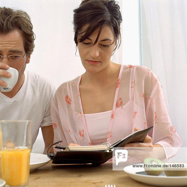 Paar mit Tagebuch beim Frühstück