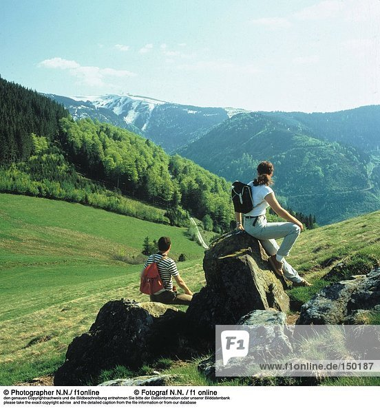 Two hikers sitting on rocks and looking at a mountain view  Schwarzwald  Germany