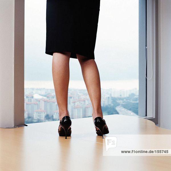 Geschäftsfrau auf dem Schreibtisch stehend