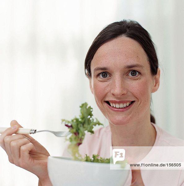 Lächelnde Frau beim Salatessen