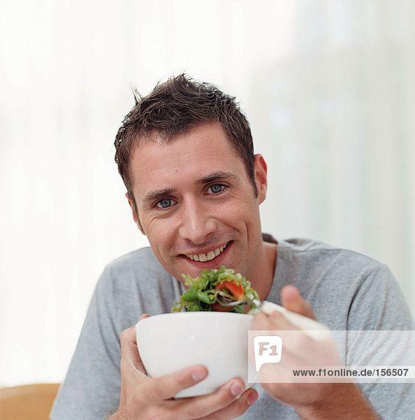 Mann  der eine Schüssel Salat isst.