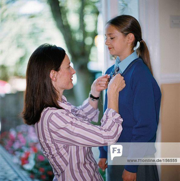 Frau zieht ihre Tochter für die Schule an