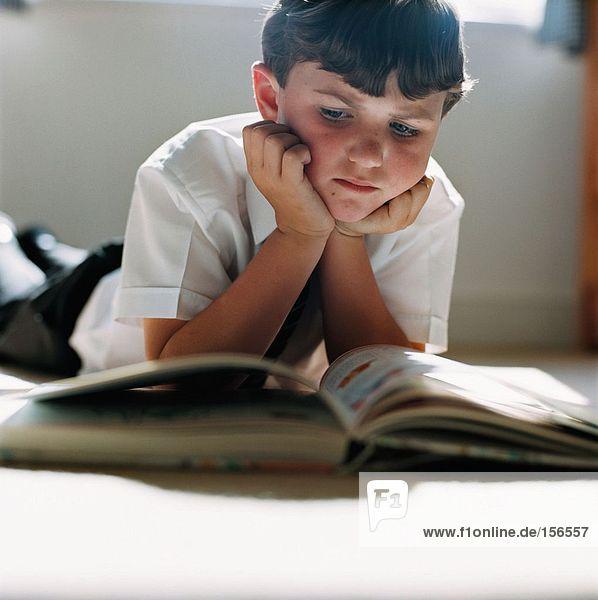 Junge liest auf dem Boden