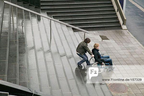 Mann hilft behinderten Menschen die Treppe hinauf