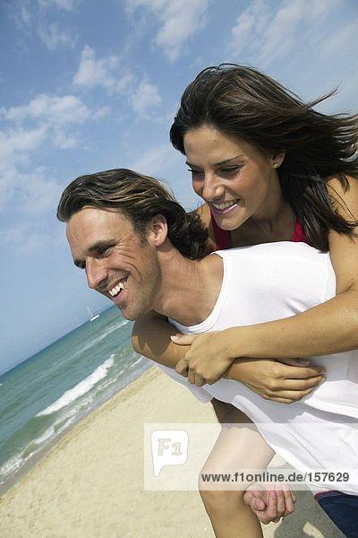 Mitte Erwachsenen Mann einzuräumen piggyback junge Frau am Strand
