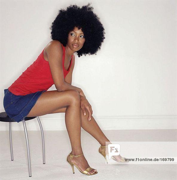 Frau mit Afro auf Hocker sitzend