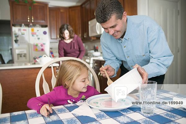 Father serving dinner for daughter