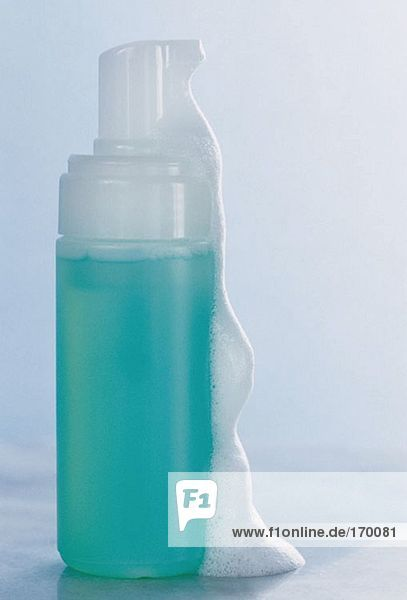 A bottle of cleanser with foam