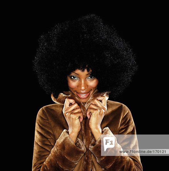 Junge Frau im Pelzmantel mit afro