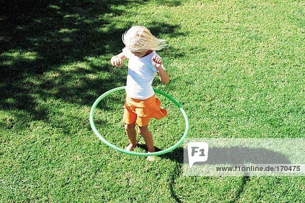 Mädchen spielt mit Hula Hoop