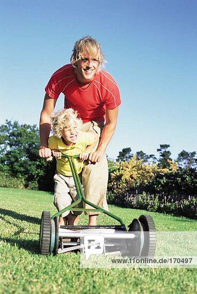 Vater und Sohn schieben Rasenmäher