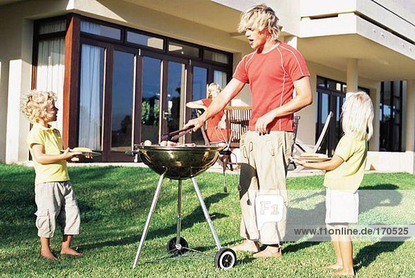 Vater beim Grillen für seine Familie