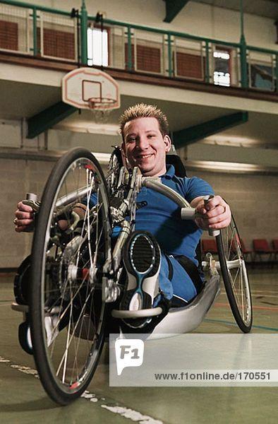 Behinderter Mann mit angepasstem Fahrrad