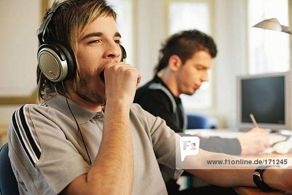 Mann im Kopfhörer gähnend