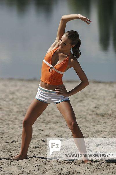 Young woman doing yoga on lake beach