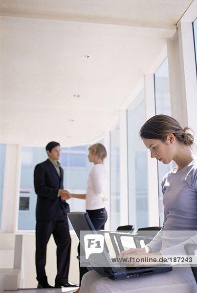 Frau mit Laptop als Kollegen Hände schütteln