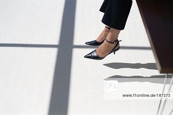 Frau baumelt mit den Füßen vom Schreibtisch