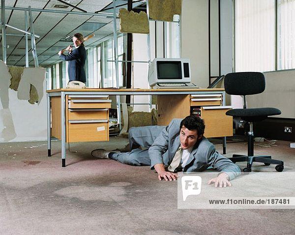 Geschäftsmann versteckt sich vor dem Angriff des Kollegen
