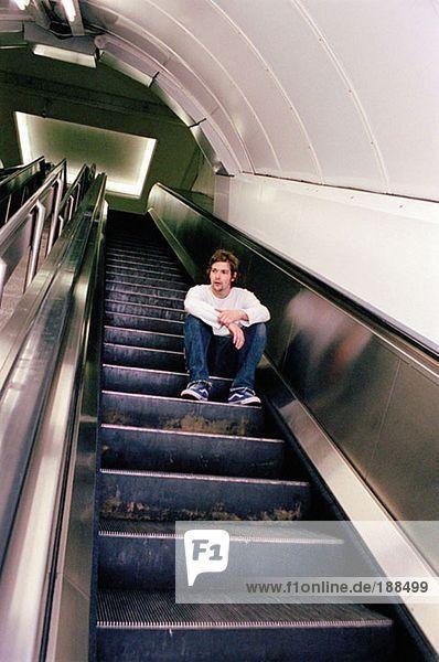 Mann auf Rolltreppe sitzend
