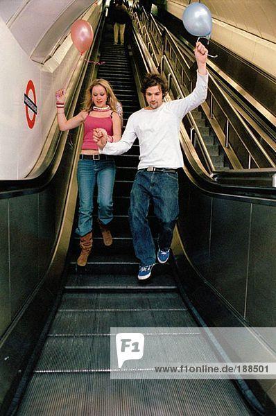 Paar mit Ballons auf Rolltreppe