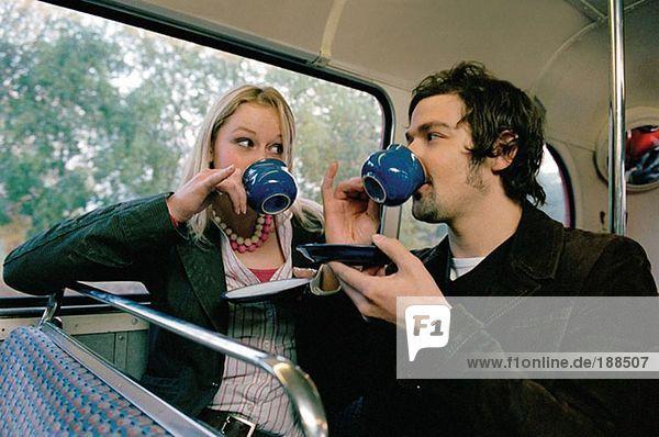Paar trinkt Tee im Bus