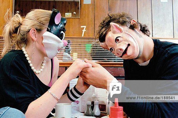 Paar tragende Gesichtsmasken im Cafe