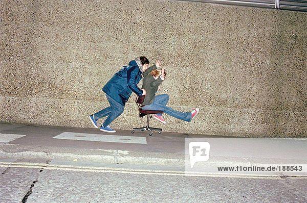 Paar spielt auf Bürostuhl