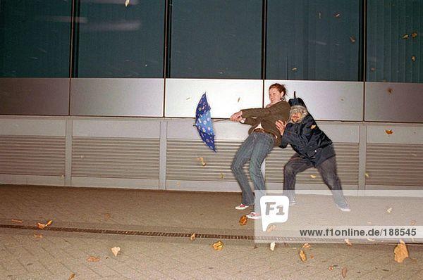 Paar mit Regenschirm im Wind