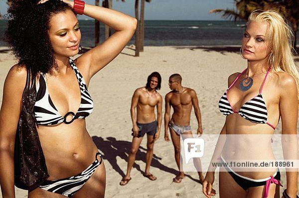 Männer  die Frauen am Strand anschauen.